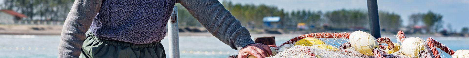 homem velho a segurar redes de pesca em barco