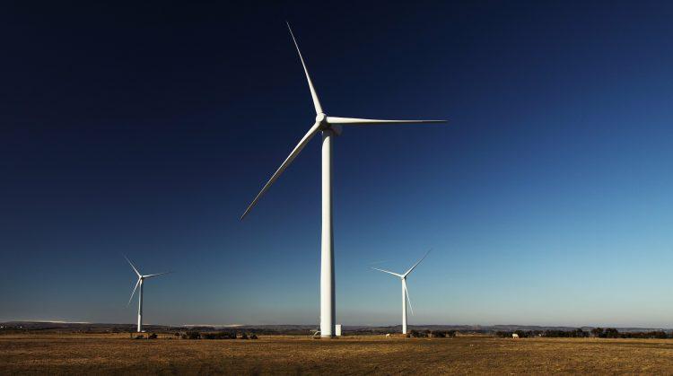 terreno plano com três ventoinhas eólicas