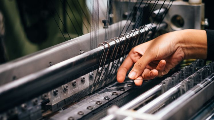 Hands of a woman working on a textile factory machine